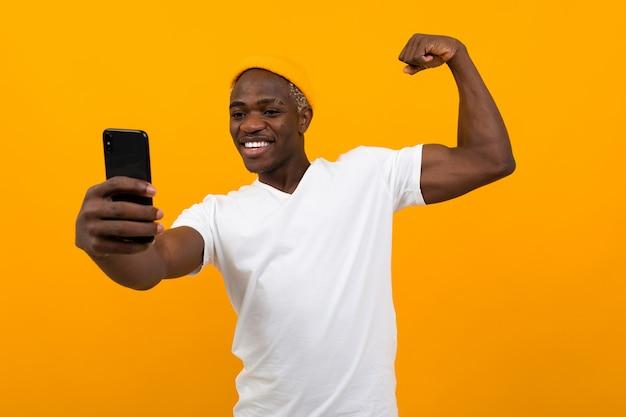 コピースペースとオレンジ色で電話でselfieを取ってハンサムな黒アメリカ人