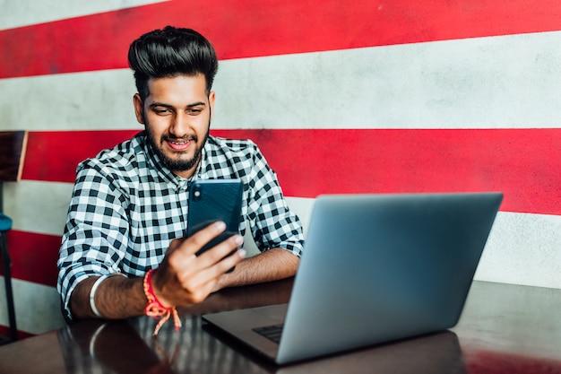 Красивый, чернобородый бизнесмен в повседневной одежде использует смартфон и улыбается, работая с ноутбуком в гастропабе.
