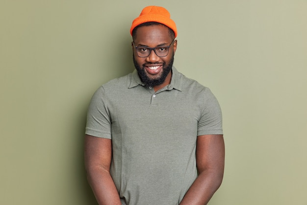 Handsome black bearded man smiles happily looks self confident at camera enjoys good day and pleasant talk wears basic t shirt orange hat and spectacles poses against dark green studio wall