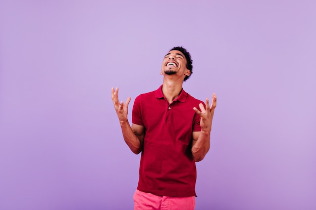 幸せを表現するハンサムな黒人の男。赤いシャツを着たのんきな黒髪の男。