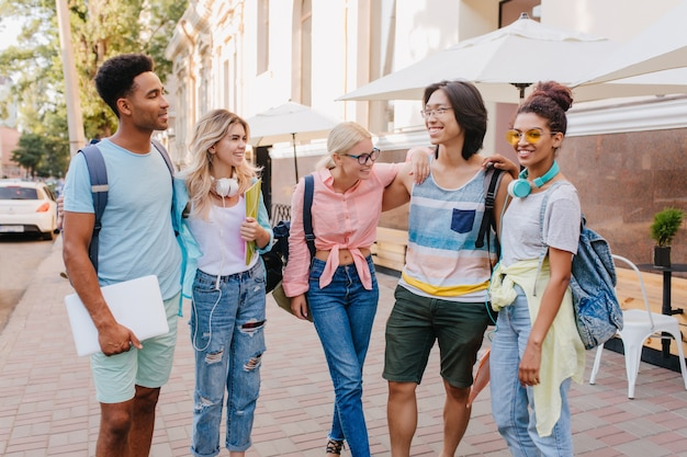 Handsome black guy with laptop looking at asian boy in glasses, which gently embracing cute girls. students in stylish clothes hanging out together on the street and laughing.