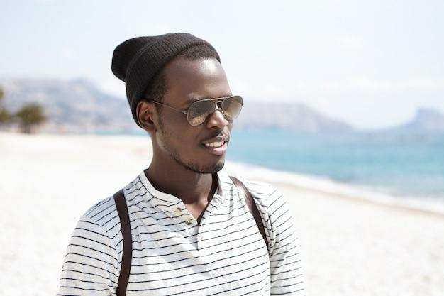 Hipster nero bello che indossa cappello elegante, camicia da marinaio, sfumature e zaino che cammina da solo sulla spiaggia urbana, ammirando il paesaggio marittimo marittimo mentre si viaggia all'estero durante le vacanze estive