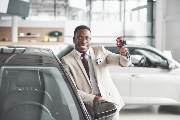Handsome black man in dealership is hugging his new car and smiling
