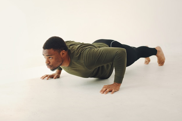 Handsome black man doing yoga on a white wall