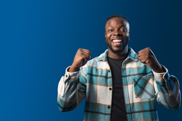 Handsome black man smiling, celebrating something with his fists raised. blue background