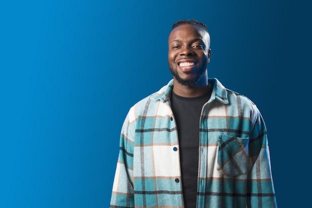Handsome black man smiling in confident pose. mid shot. blue background
