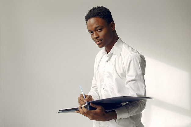 Handsome black man standing on a white wall