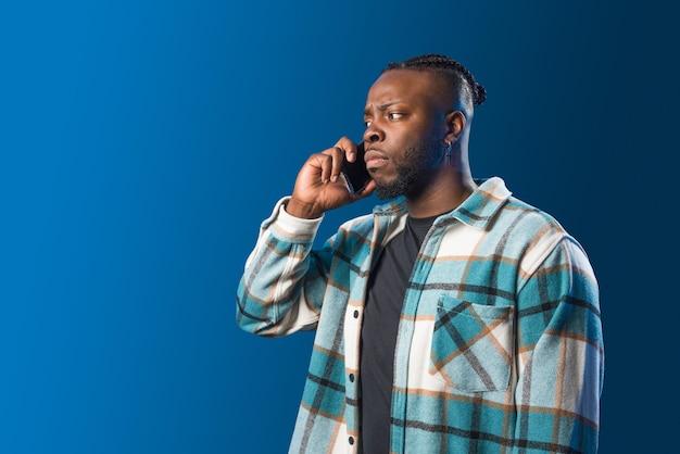 휴대폰으로 통화하는 잘생긴 흑인 남자가 걱정됩니다. 미드샷. 파란색 배경입니다.