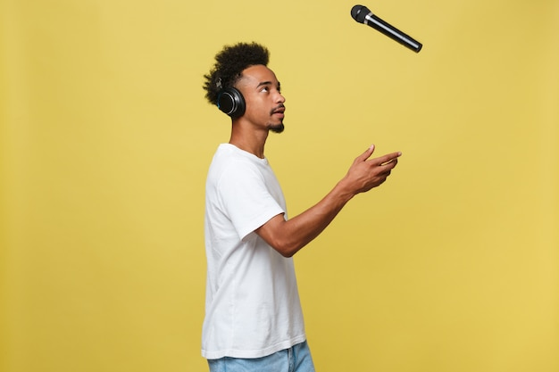 Handsome black man throwing a microphone and singing.