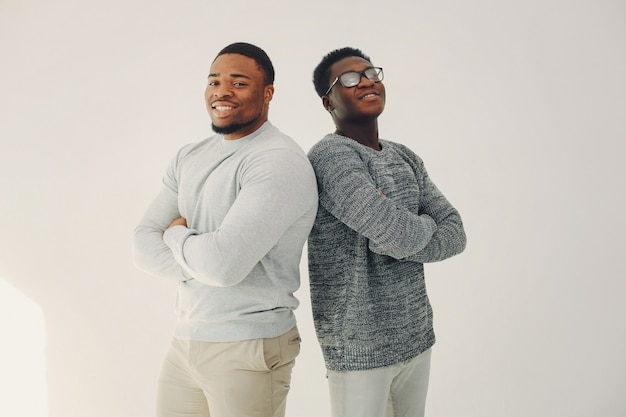 Handsome black men standing on a white wall