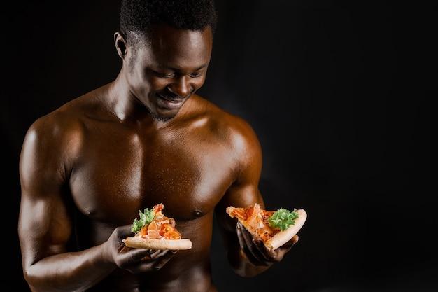 2枚のピザを持ったハンサムな黒人裸の男がより良いものを選ぶ