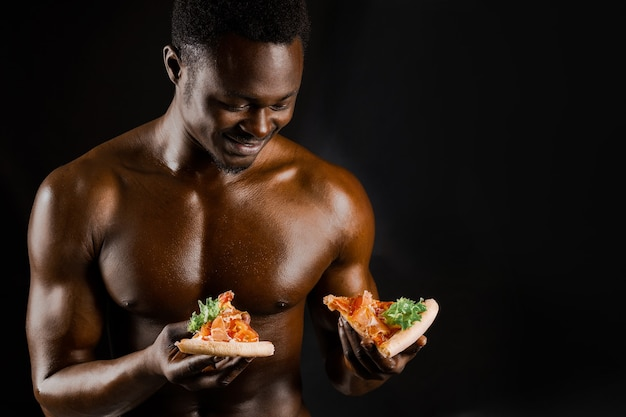 Handsome black naked man with 2 pieces of pizza choose better one