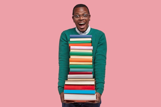 Handsome black young man poses against pink studio background, carries textbook, reads much, prepares for lesson