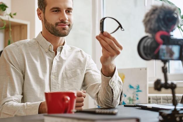 Красивый блогер показывает умные часы на камеру во время записи нового видео для своего ютуба.