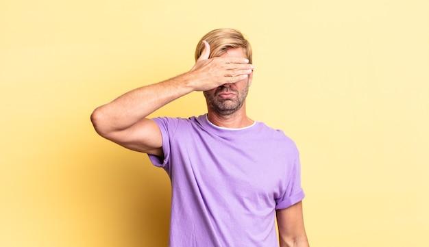 片手で目を覆っているハンサムな金髪の成人男性は、恐怖や不安を感じ、不思議に思ったり、盲目的に驚きを待っています