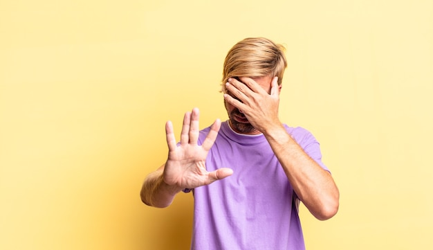 Handsome blond adult man covering face with hand and putting other hand up front to stop camera, refusing photos or pictures