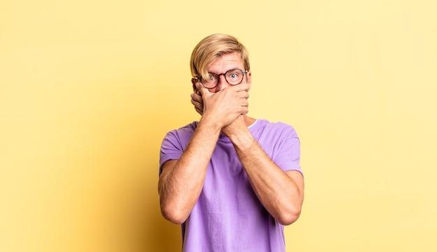 잘생긴 금발 성인 남자는 충격을 받고 놀란 표정으로 손으로 입을 가리고 비밀을 유지하거나 죄송합니다