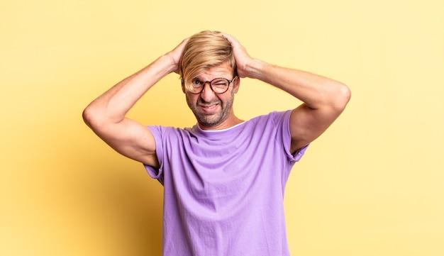 Красивый взрослый блондин чувствует себя разочарованным и раздраженным, усталым от неудач, сытым по горло скучными, скучными задачами