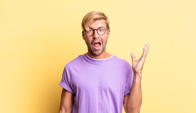 Красивый белокурый взрослый мужчина чувствует себя счастливым, удивленным и веселым, улыбается с позитивным настроем, реализует решение или идею