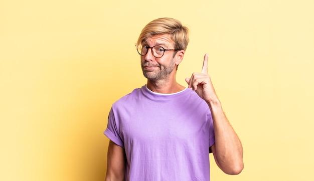 Красивый белокурый взрослый мужчина, чувствуя себя гением, гордо подняв палец вверх, реализовав отличную идею, говоря: «эврика»