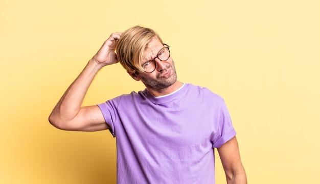 Красивый взрослый блондин, чувствуя себя озадаченным и сбитым с толку, почесывая голову и глядя в сторону