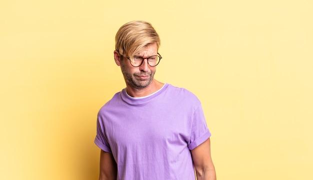 ハンサムな金髪の成人男性は、悲しみ、動揺、または怒りを感じ、否定的な態度で横を向いて、意見の相違に眉をひそめています