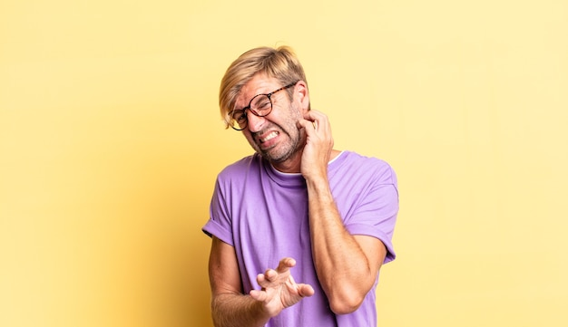 Красивый белокурый взрослый мужчина чувствует себя напряженным, расстроенным и усталым, потирая болезненную шею, с встревоженным, встревоженным взглядом