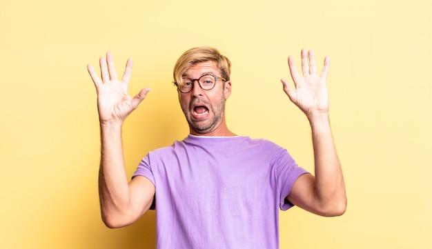 Красивый белокурый взрослый мужчина чувствует себя ошеломленным и напуганным, боится чего-то пугающего, с раскрытыми руками и говорит: «держись подальше»