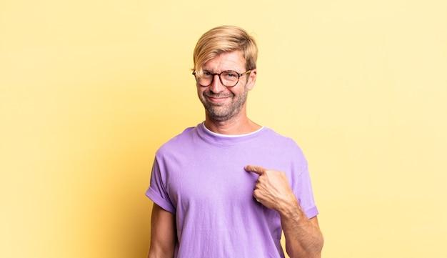 Красивый белокурый взрослый мужчина выглядит гордым, уверенным и счастливым, улыбается и указывает на себя или делает знак номер один