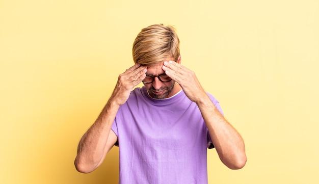 Красивый белокурый взрослый мужчина выглядит напряженным и расстроенным, работает под давлением с головной болью и обеспокоен проблемами