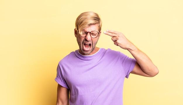 不幸でストレスを感じているハンサムな金髪の成人男性、手で銃のサインを作る自殺ジェスチャー、頭を指して