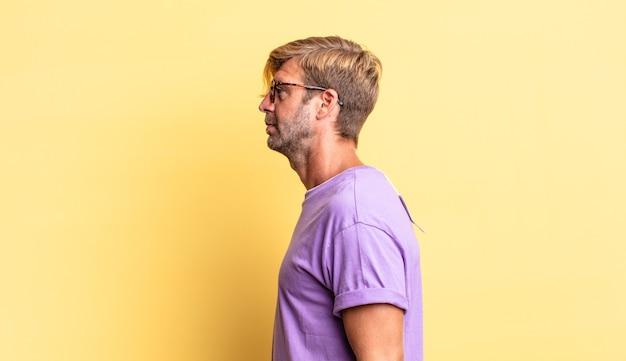 Красивый белокурый взрослый мужчина на виде профиля, желающий скопировать пространство впереди, думать, воображать или мечтать