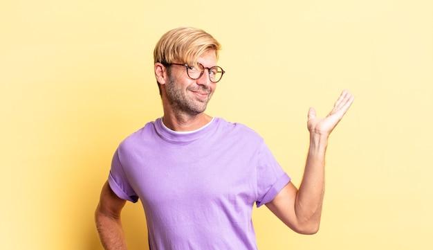 Красивый белокурый взрослый мужчина улыбается, чувствует себя уверенным, успешным и счастливым, показывая концепцию или идею на копировальном пространстве сбоку
