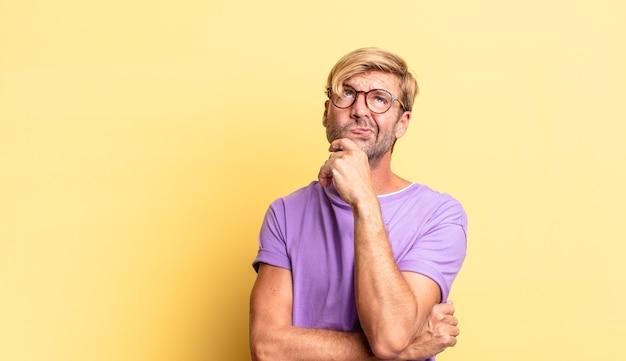 Красивый белокурый взрослый мужчина думает, чувствует себя сомнительным и сбитым с толку, с разными вариантами, задаваясь вопросом, какое решение принять