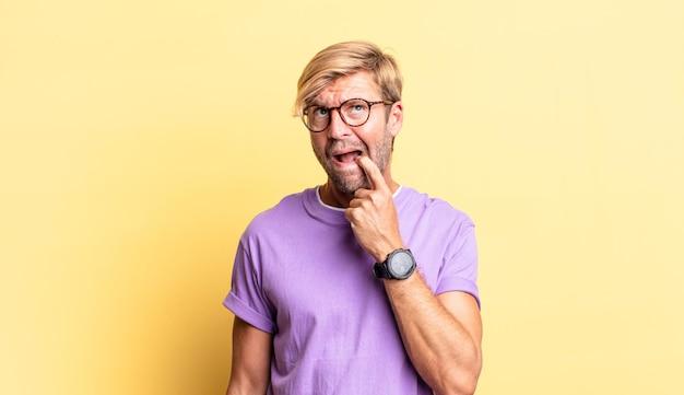 コピースペースの方を向いて、驚いた、緊張した、心配した、またはおびえた表情のハンサムな金髪の成人男性