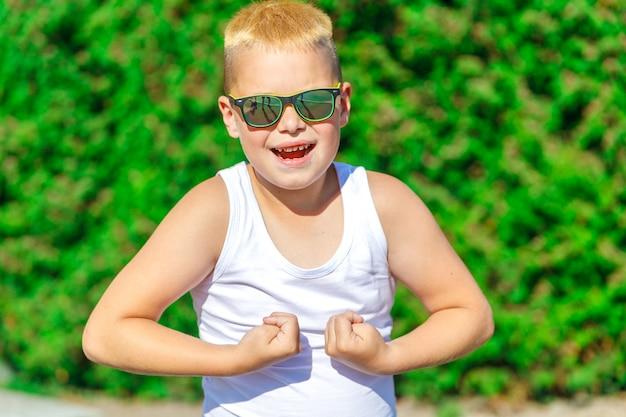 サングラスをかけたハンサムな金髪の少年は、夏の自然の中で筋肉を示しています