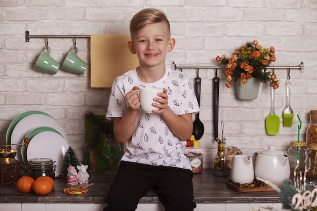 A handsome blond boy is sitting on the kitchen table with a big white cup in his hand. funny photo
