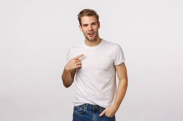 Handsome blond guy with blue eyes and white t-shirt pointing himself