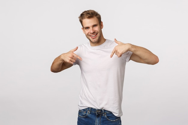 Handsome blond guy with blue eyes and white t-shirt pointing to himself