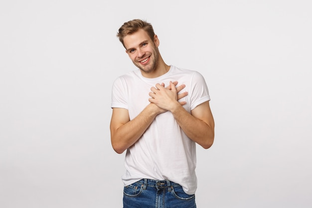 Handsome blond guy with blue eyes and white t-shirt pressing hands to heart