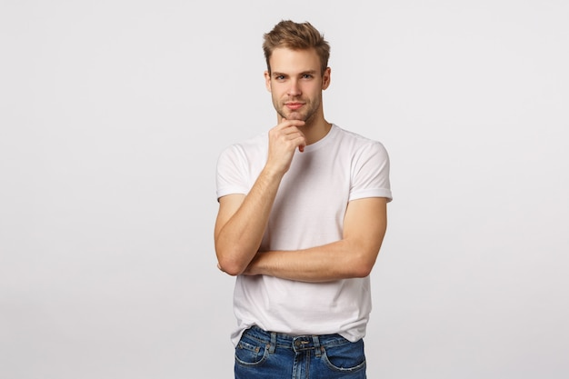 Handsome blond guy with blue eyes and white t-shirt thinking