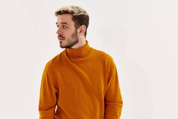 Handsome blond man looking to the side orange sweater closeup portrait