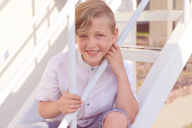 夏に白い階段の上に立って笑っている白いシャツを着たハンサムなブロンドの少年。高品質の写真