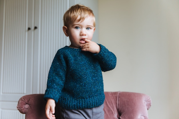 Handsome blonde little child keeps finger in mouth, looks with his blue appealing eyes