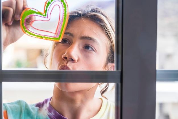 ハンサムなブロンドの長い髪の若い男の子 10 代の若者が家の窓に絵を描き、色の炉をする