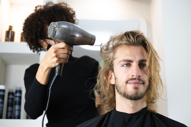 Handsome blonde male client getting haircut by black female hairdresser