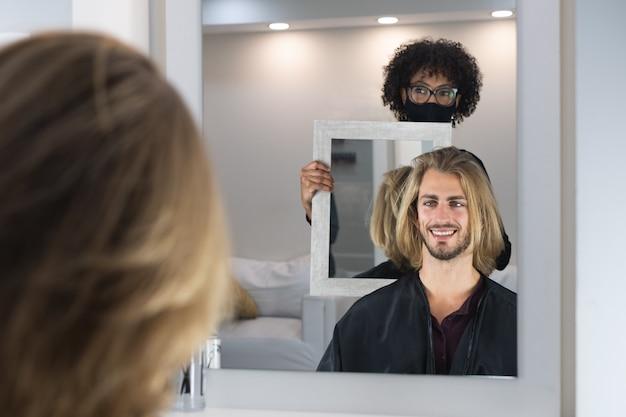 黒人女性の美容師によって散髪されているハンサムなブロンドの男性のクライアント
