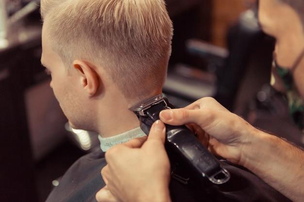レトロな理髪店、背面図で美容師によって彼の髪をカットされているハンサムなブロンドの男