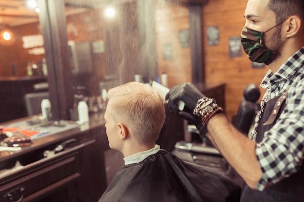 レトロな理髪店で美容師に髪を切ってもらうハンサムなブロンドの男