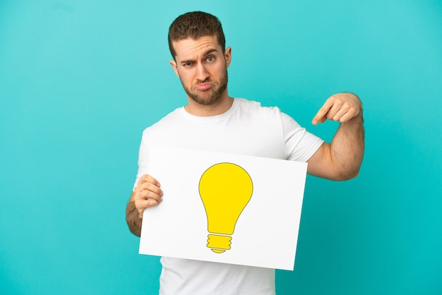 Handsome blonde man over isolated blue background holding a placard with bulb icon and pointing it